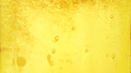 Extreme close up background of pouring lager beer with bubbles and froth over the top in glass mug, overfill and run out, low angle side view, slow motion