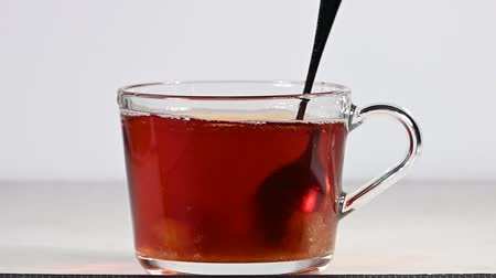 Close up stirring cubes of brown sugar with metal spoon in transparent glass cup of red black tea over white background, low angle side view, slow motion Videos