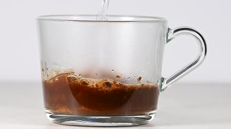 Close up pouring hot water in glass cup with granules of freeze dried instant coffee over white background, low angle side view, slow motion