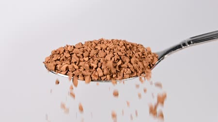 instante : Close up pouring granules of freeze dried instant coffee from metal spoon over white background, low angle side view, slow motion Stock Footage