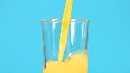 Close up pouring fresh yellow orange juice in drinking glass over vivid blue color background, low angle side view, slow motion Videos