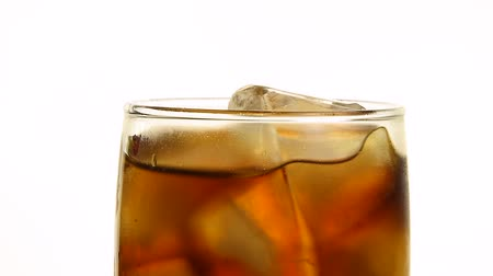 Extreme close up full glass of carbonated cola soft drink with ice cubes spinning, isolated on white background, low angle side view, slow motion