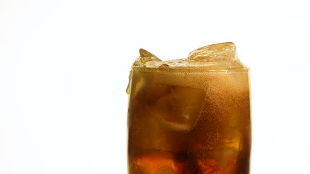 Extreme close up of pouring carbonated cola soft drink in transparent glass with ice cubes until full over white background, low angle side view, slow motion