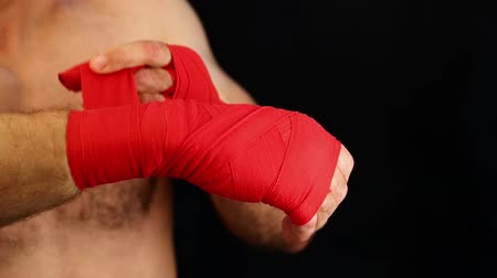 apertado : Close up man boxer wrapping red hand wraps over wrists preparing for fight, over black background with copy space, low angle view Vídeos