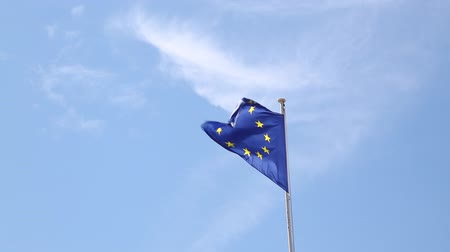 flap : Close up flag of EU, European Union waving and blowing in the wind over blue sky, low angle view