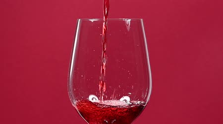 züccaciye : Close up pouring and splashing red wine in big wineglass over burgundy maroon red background, low angle side view, slow motion