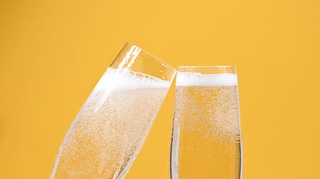 karbonatlı : Close up pouring two full glasses of white champagne sparkling wine from bottle over vivid yellow background, low angle side view, slow motion
