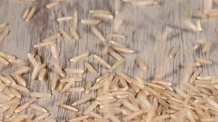 bounce : Close up background of dried unpolished brown rice grains falling on wooden table surface, slow motion