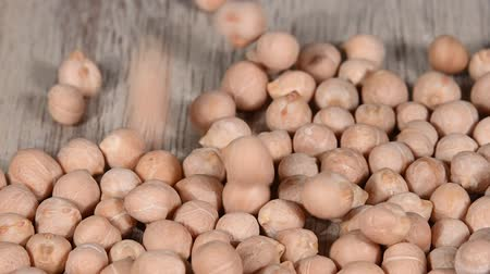 bounce : Close up background of dried chickpea beans falling on wooden table surface, slow motion Stock Footage
