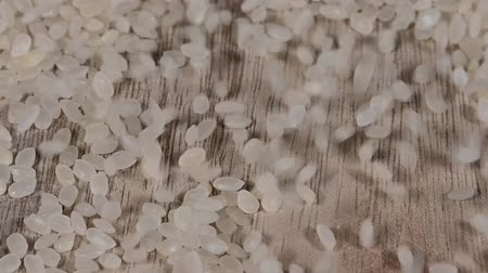 sponka : Close up background of dried Japanese sushi rice falling on wooden table surface, slow motion