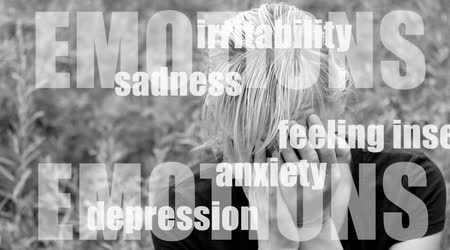 stres : Monochrome photo of a middle aged woman with hands covering her face is sitting on the bench outside. On the footage are moving words denoting the effects of stress on body, emotions and behavior. Wideo