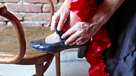 přezka : Closeup view of a Flamenco dancer with her foot on an old chair and putting on the black old shoe.