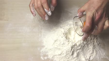 Preparation for baking - inserting the yolk into a pile of flour
