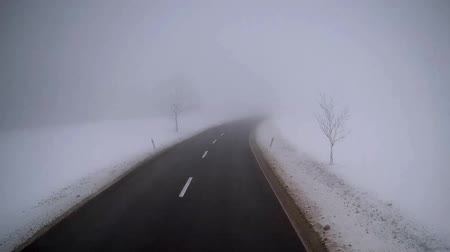 Exclusive view from truck driver`s cab. Accelerated motion footage of driving truck on empty road in foggy winter day