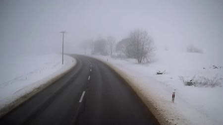 Exclusive view from the cab of a truck driver. Accelerated ride on empty road in foggy winter day