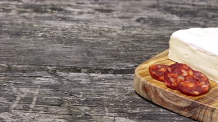 caloric : Footage showing a moving camera focusing on the old wooden desk with hot sausage Chorizo, tomatoes, garlic bulb and a piece of the Petite Brie cheese.