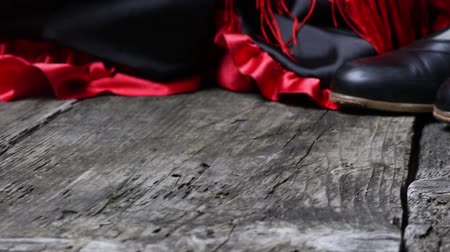 Moving camera footage of clothing for Flamenco dance. Black shoes, red scarf with tassels are on the old wooden desk.