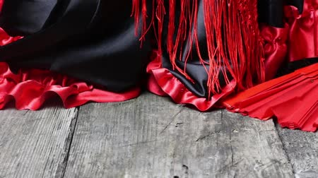 Moving camera footage of clothing for Flamenco dance. Clothes, red scarf with tassels and red fan are on the old wooden desk. Camera is moving from the left to the right.