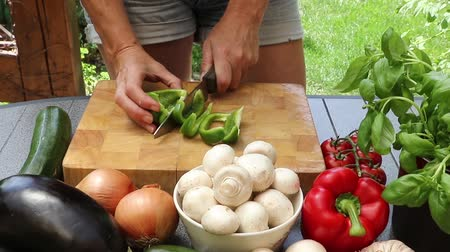 bakłażan : Woman cutting green pepper on a wooden board surrounded by fresh vegetables outdoors