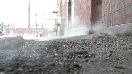 unearthed : Steam randomly emitting from concrete in a downtown urban setting on a cold winter day with natural lighting on buildings in the background.