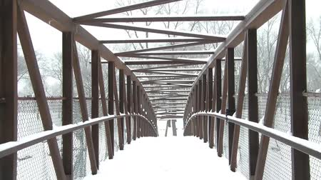 ürpertici : Looking through snowy bridge in winter on gloomy grey day yielding abstract view from riverbank.