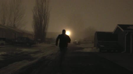 közepes : In a foggy alley during winter, a masked man runs away and looks back as if he has done something wrong.