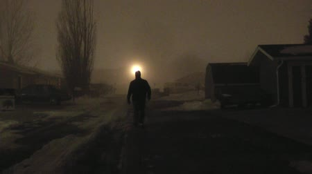испуг : Unidentifiable, dark dressed man approaching camera slow and steady in eerie fog, set at night, and in a narrow alley.