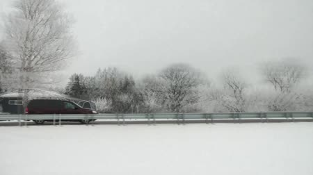 low lighting : Video of two cars cruising quickly over a snowy bridge in the middle of winter, leaving Minnesota, and entering North Dakota.