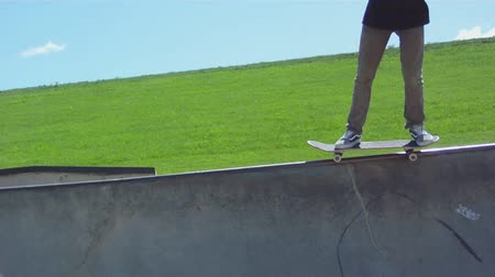 zajímavý : Skateboarding trick up wall, and then dropping back down into pool in summer sun.
