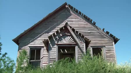 apodrecendo : Clip of abandoned old farmhouse with faded wood siding, tall weeds in foreground, and a cloudless blue sky in background.