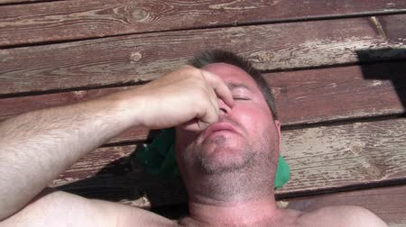 çinko : Man applies sunscreen to his nose while suntanning outside on his deck with rustic floor as background.