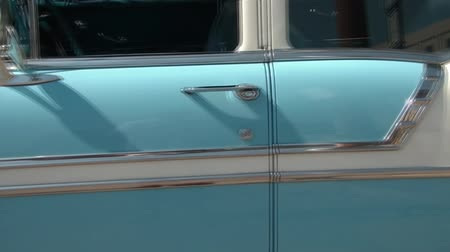 engineered : Pan of baby blue and white classic car in bright sunshine along drivers side door.