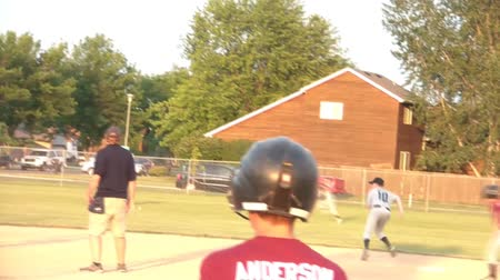 Baseball game with batter hitting pitch only to bat in a run for his respective team.