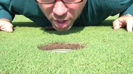focalizada : Businessman blows golf ball into hole on green after a couple of attempts, pulls ball out, gets up, and replaces yellow pin, in sunlight.