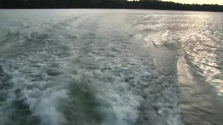 sightly : Clip of wake left behind by boat motor when boat is moving, and then a pan upward to surrounding lake scenery. Stock Footage