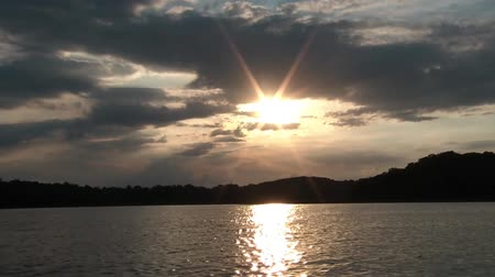 bezmotorové létání : Clip of bobbing boat view on lake with beautiful sunset and hills in background. Dostupné videozáznamy