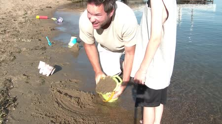miłość : Boy and his father dump a bucket of sand on beach near waters edge in order to create a sandcastle during summer afternoon. Wideo