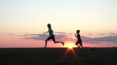 miłość : Boy chases girl on small hill at sunset with camera panning across sun, and girl never getting caught. Wideo