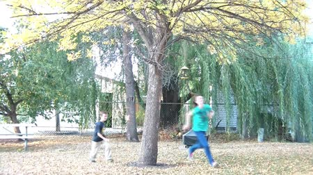 incecik : Autumn clip of girl hiding behind a yellow tree until the boy finds her, he then proceeds to chase her around (with both laughing), brown leaves covering grass.