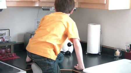alcançando : Boy hops up on counter and sits, taking top off of cookie jar, and then proceeds to pull cookie out.