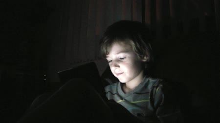 szőke : Young boys face is illuminated by the screen of a handheld video game in the dark.