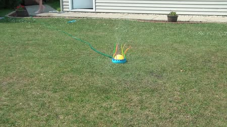 ailelerin : Young boy running and jumping over water sprinkler on a summer afternoon. Stok Video