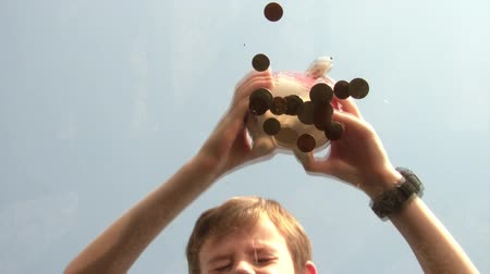 holding onto : Boy shaking piggy bank while coins randomly fall out onto surface, blue sky background with angled sun.