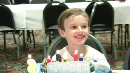 день рождения : Boy smiles for pictures and waits to blow out his candles at his sixth birthday party. Стоковые видеозаписи