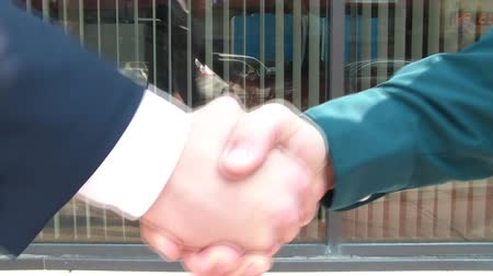 милый : Business handshake by two businessmen in downtown urban setting during sunny afternoon.