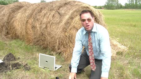 gravata : Businessmans foot is stuck in hole in rural setting as he pleads for help while still trying to get leg out, crooked sunglasses, hay bail and laptop computer in frame.
