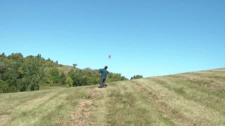 gravata : Businessman throws up pink ball into air atop green hill in sun, letting loose of his stress, with scenic hills, and blue sky in background.