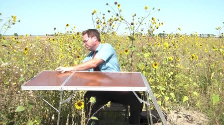 подсолнухи : Businessman in sun has office set up in wild sunflower field; puts laptop in case, and then folds up table, grabbing case, and chair to leave.