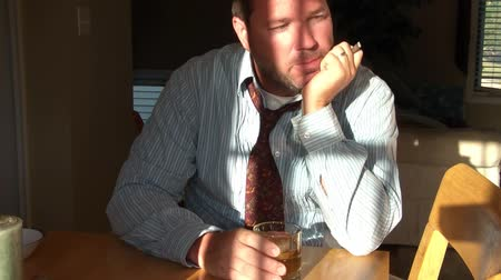 cigar : Clip of businessman with tie sitting at table after work sipping whiskey from glass and smoking. Stock Footage