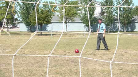 zaoblený : A man in business clothes lines up a goal with hand, and then proceeds to kick a soccer ball into goal in afternoon sunlight.